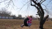 elbow : A woman on a swing in the village Stock Footage