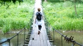 wood : girl traveler standing on a bridge across a mountain river. The tourist walks