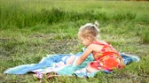 kürk : A little blonde is sitting on a plaid on the grass.