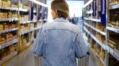 gıda maddeleri : Woman shopping at the supermarket, follow shot from back of young woman with trolley in shopping center.