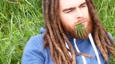 casual sitting : handsome young man with dreadlocks and a green leaf of cannabis in the mouth Stock Footage