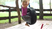 lying on front : Little blond girl riding a tire