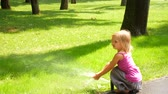 шланг : Little girl in the park under the drops of watering pad. Стоковые видеозаписи