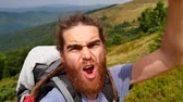 A man does selfie in the mountains. Joyous video, turn in a circle. Stockvideo