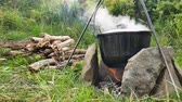Cooking outdoor food in tourist pot at bonfire. Process preparing camping food on burning fire while hiking to wild nature. Stockvideo