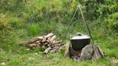 utensili da cucina : Cooking outdoor food in tourist pot at bonfire. Process preparing camping food on burning fire while hiking to wild nature. Filmati Stock