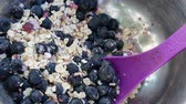 뮤 즐리 : CLOSE UP Cereal with blueberries being scooped with a spoon for breakfast.