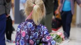 voyage affaire : Little girl with a bouquet of roses in the airport lounge. Vidéos Libres De Droits