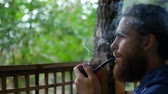 tyton : Close up of attractive man with beard smoking on the beach. Outside. Portrait.