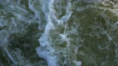 boşaltmak : Streams of water on the river dam splashing out from the gateway and form waves. Close-up.