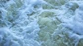 descarga : Streams of water on the river dam splashing out from the gateway and form waves. Close-up.