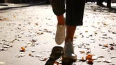 探検家 : Slow Motion, Girl Walking in Autumnal Park on Orange Leaves, Scattering Kicking Leaves, Autumn, Shod in White Sneakers and Short Jeans, Leaves Flies From Step.