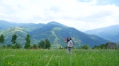 мечты : A young man with dreadlocks playing with a model airplane in the mountains.