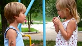 generosità : Friends eat chocolate in the park. The girl shares with the boy.
