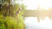 idílio : Child girl catches fish in the river with a stick. Beautiful sunset diffused light.