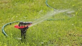 Lawn sprinkler pulverizing water on the green lawn, close-up, HD 1080p
