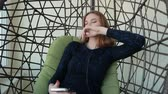 кулон : Beautiful young woman sits in a pendant chair with the phone and listens to music