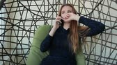 кулон : Beautiful young woman sits in a chair and talking on the phone