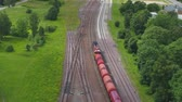 poskytování : Oil and gas, transport by train. Beautiful summer nature and cargo train, runs through the city. Aerial footage.