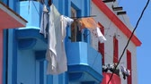 clothe : Clothes Hanging from Window Drying. Drying Clothes on a Sunny day, Handing from Colorful Building. Stock Footage