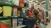 go cart : Young blond woman walk along shelves in supermarket and buy plastic bucket Stock Footage