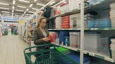 go cart : Young blond woman walk along shelves in supermarket and buy plastic container