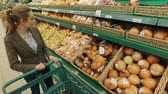 refrigerated : Young blond woman walk along shelves with fruits in supermarket