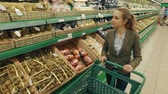 refrigerated : Young blond woman walk along shelves with fruits in supermarket and buy papaya Stock Footage