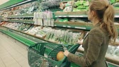 refrigerated : Young blond woman walk along shelves with greenery in supermarket Stock Footage