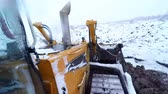 bauxite : Bulldozer machine working with ground on snow winter day. View from cabin