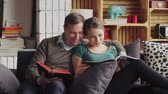 family values : Young couple on sofa reading books, cuddling and having fun