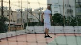 relaxation : View through a grid fence tired athlete at outdoor workout