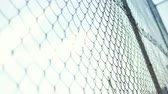 grid : Blows on mesh fence with mens hands. Angry bald man beats hands on a grid fence