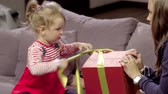 suddenness : Mom together daughter open holiday present box sitting on couch on New Year eve