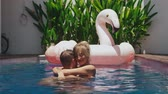 honeymoon : Young couple swimming in hotel pool in tropical country