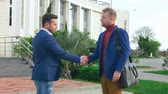promessa : Two promising young businessmen greeting each other with a handshake