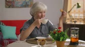 swiping : Happy elderly woman in casual clothes drinking tea and eating cookies