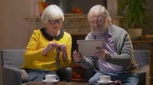 independent : Elderly couple talking over video calling using tablet with their children Stock Footage