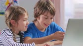 memnun : Boy and girl watching cartoons on laptop computer