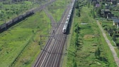 Two trains moving by rail in opposite directions through countryside, aerial