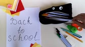 block notes : Packing a pencil case back to school, putting in it various school stuff and giving thumb-up. Time-lapse