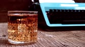 cinemagraph of some bubbles emerging in a glass with liquor placed in a rustic wooden desk with an old typewriter in the background Vidéos Libres De Droits