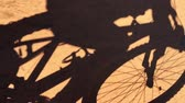 the silhouette of a young man riding a mountain bike on a dirt road Stok Video