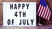 cinemagraph of a lighting lightbox with the text happy 4th of july and an american flag on a rustic wooden background