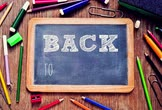 the text back to school being written in a wooden-framed chalkboard placed on a rustic wooden table full of markers, pencil crayons and other school supplies Vidéos Libres De Droits