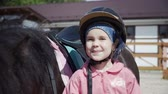 dressage : Little girl is looking at camera, posing with the black pony and smiling.