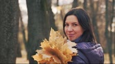 Happy young pretty brunette woman is posing with the bouquet of autumn leaves in the park.