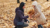 Little girl gives mom a bouquet of autumn leaves in the park.