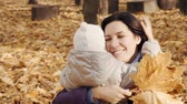 Happy woman hugging her little daughter in the autumn park. Stock Footage
