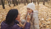 Mother is applying the gloss on the daughters lips in the autumn park.